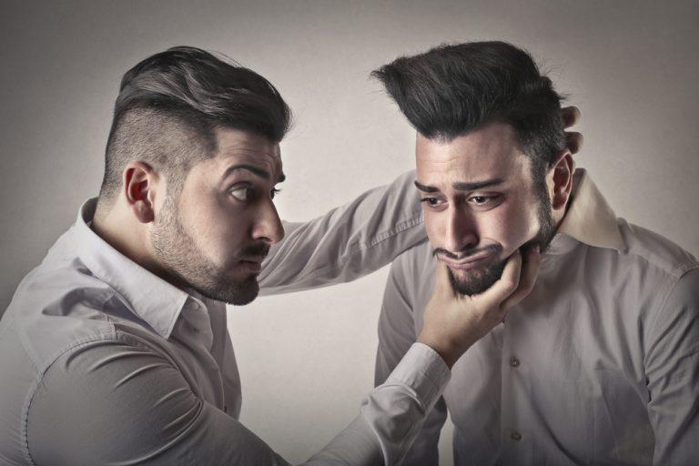 Homem com expressão ameaçadora segura a cabeça do outro forçando um sorriso